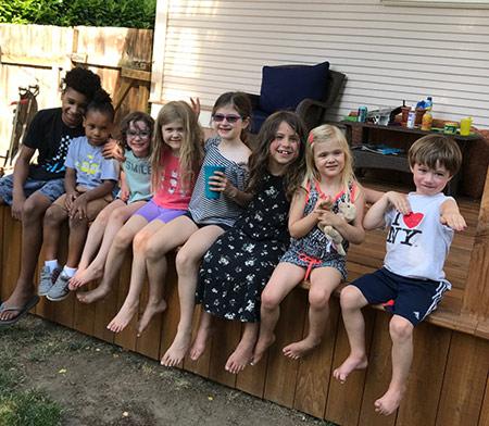 Eight Concordia Kids News kids sitting on a ledge