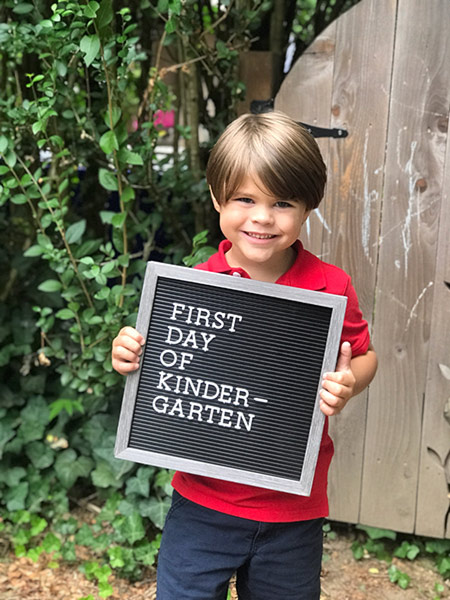 boy holding sign for first day of kindergarten