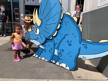 Toddler and mom standing next to Albertasaurus on Alberta Street.